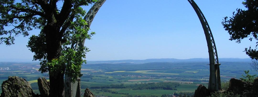 Blick durch den Adlerbogen auf die bewaldeten Kuppen der Haardt.