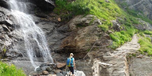 Über Bergwiesen und vorbei an Wasserfällen geht es in Richtung Tribulaunhütte.