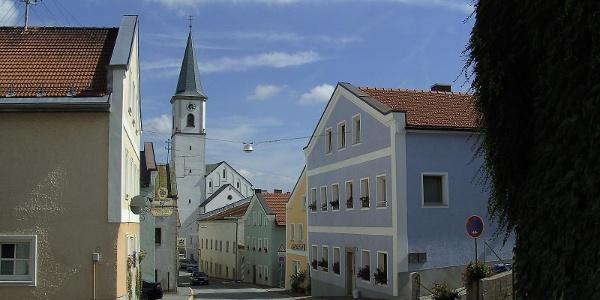 Die Marktstraße in Perlesreuth mit den bunten Häusern und dem Kirchturm.