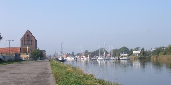 Wir blicken am Ufer des Ryck in Greifswald auf Hafen und alte Speicher.