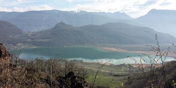 Panoramablick über den Kalterer See. Im Hintergrund die Leuchtenburg vor den verschneiten Gipfeln des Schwarz- und Weißhorns
