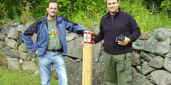 Pilgrims by pole with the Saint Olav mark