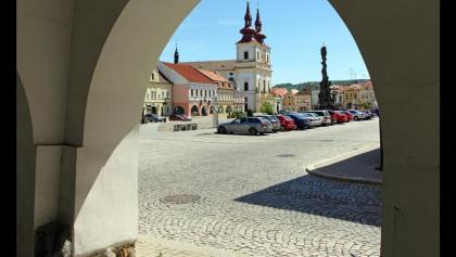 Kostel Povýšení sv. Kříže (Heiligkreuzkirche) und Morový sloup (Dreifaltigkeitssäule) am Mírové náměstí (Friedensplatz) von den Arkaden des Šlikovský dům (Schlick-Haus)