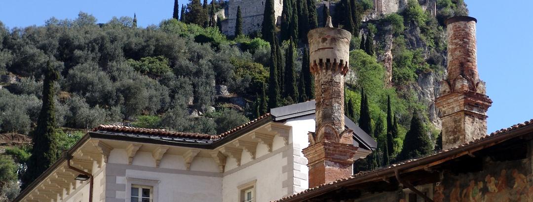 Die Schornsteine des Palazzo Marchetti mit der Burg im Hintergrund