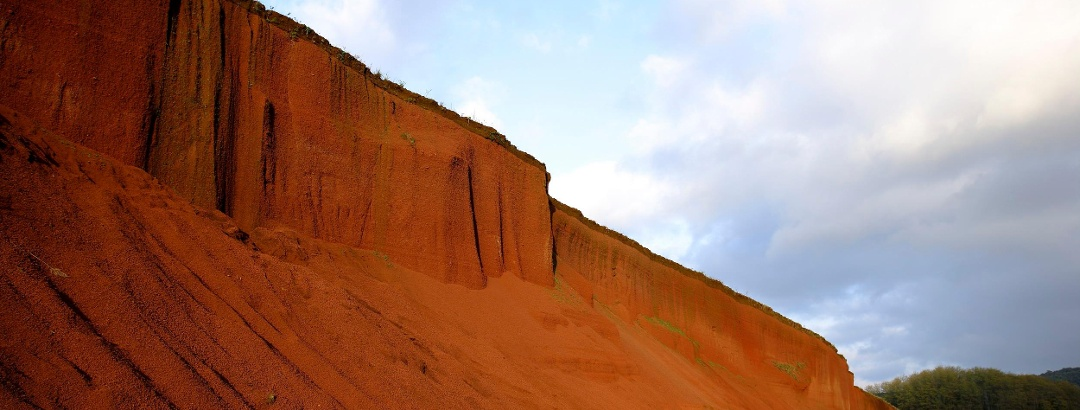 Bei dieser Wanderung geht es über rote Erde und an Vulkankratern vorbei.
