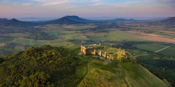 Zrúcanina hradu Csobánc na drónovom zábere. Na brehu Balatonu vidíme rad tvrdošov