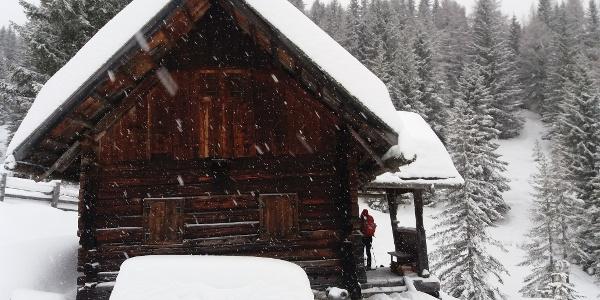 Das ältere Gebäude aus dunklem Holz hat ein Vordach vor der Hüttentür.