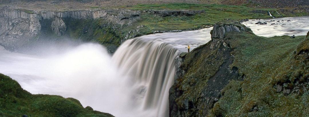 Wanderer steht am beeindruckenden Hafragilsfoss in Island