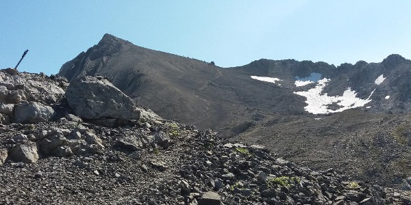 Hinter dem großen Steinmann: Blick auf den Gipfel und den Grenzübergang.