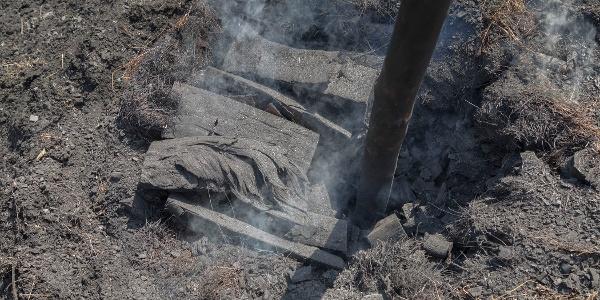 Köhler bei der Arbeit am schwelenden Kohlenmeiler mit Holzstange