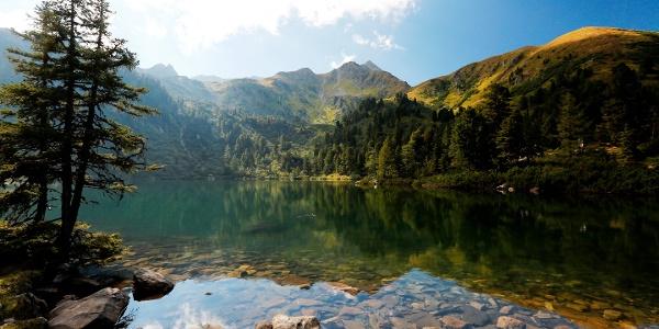 Der sonnenbeschienene Gipfel des Hauseck spiegelt sich im Großen Scheibelsee