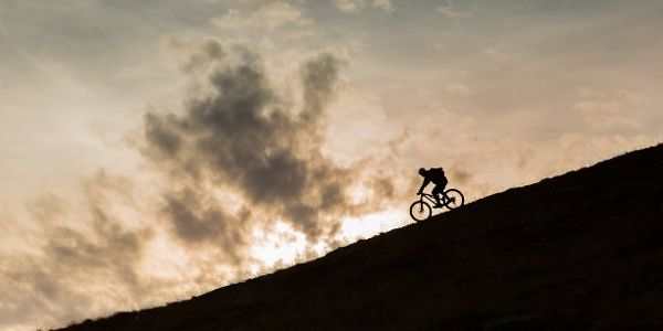 Person on a mountain bike descending a slope at the end of the day in the Lötschental