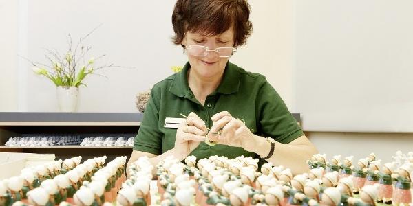 Eine Kunst-Handwerkerin bemalt filigrane Blumenkinder