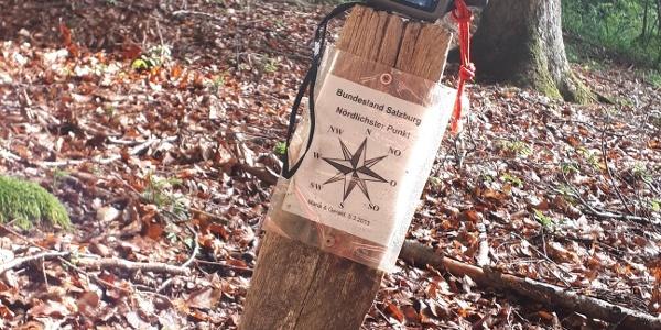 Startpunkt, ein Holzpflock mit einem weißen Küberl drauf; Hinweis darunter