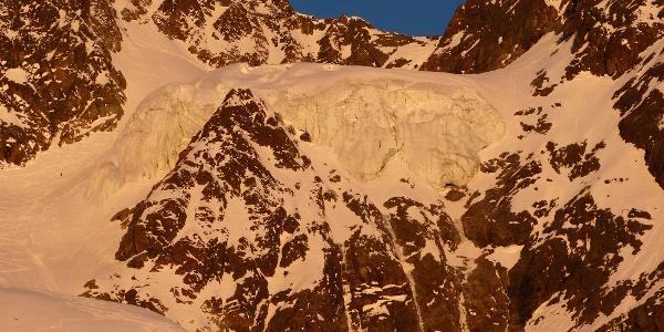 Der mächtige Hängegletscher, links zum Größenvergleich ein Skibergsteiger im Aufstieg.
