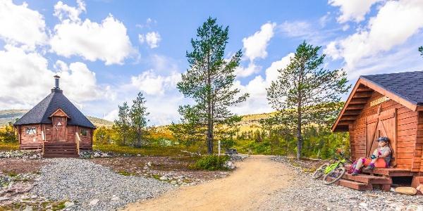 Maastopyöräilijä tauolla Tuomikurun kodan pihapiirissä. Kota sijaitsee maisemallisella paikalle Yllästunturissa puurajassa.