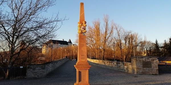 Postmeilensäule vor der Elsterbrücke mit Blick zum Schlossberg