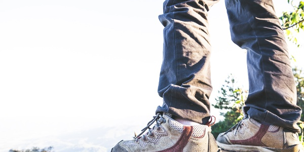 hiking shoes in action on a mountain desert trail path. Close-up of male hikers shoes.