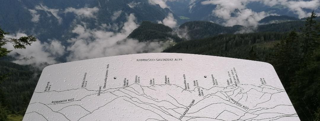 Info-Tafel bei der Bärenhöhle mit Blick nach Süden zu den Steiner Alpen (Etappen 5 und 6 des Julius-Kugy-Dreiländerweges)