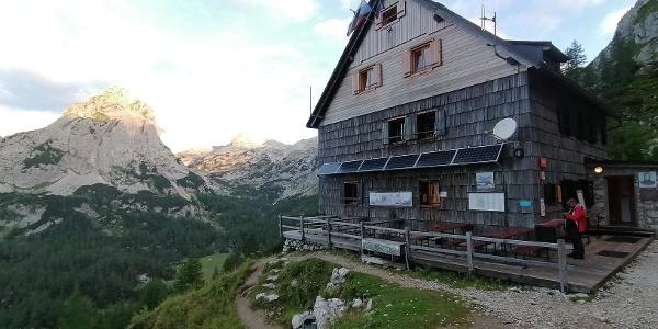 Aufbruchstimmung zur 11. Etappe beim Vodnikov dom na Velem polju – dahinter das Triglav-Massiv und Mišelj vrh (li)