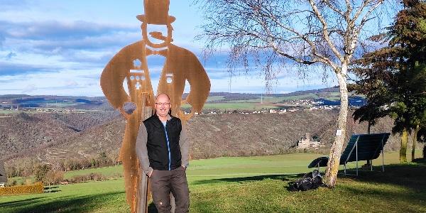 Der Quetschehannes an der Krähenhütte. Im Hintergrund Burg Katz.