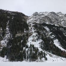 Der Ausstieg der langen Variante ist auf dem Bild erkennbar. Oben an der Säule rechts vorbei und in einer Kurve zu den vereinzelten Bäumen.
