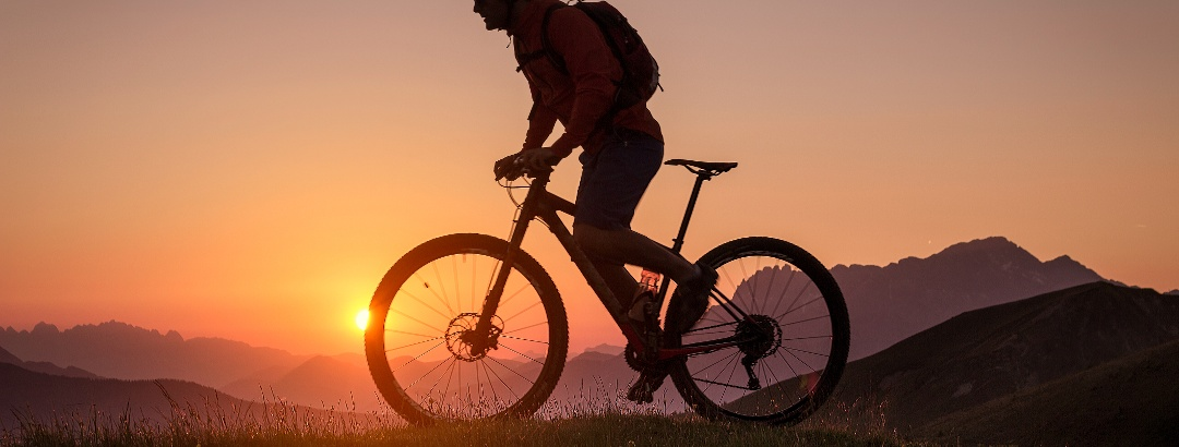 Silhouette of a male mountainbiker at sunset in the mountains