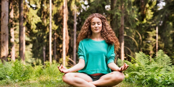 Beautiful girl practices yoga in the morning forest.