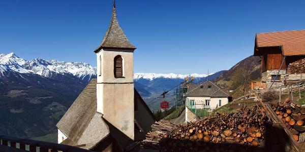 """Die Wallfahrtskirche """"Zum Heiligen Martin"""", im Hintergrund die Seilbahn von Latsch hoch nach St. Martin im Kofel"""