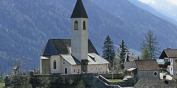 Die Pfarrkirche St. Walburg steht erhöht auf einem Hügel. Ringsum liegen verstreut Bauernhöfe und Wohnhäuser.