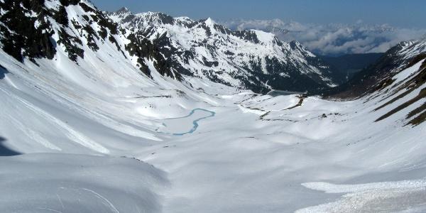 In der Scharte mit Blick zurück über das Aufstiegsgelände - unten der teilweise zugefrorene Plenderlesee