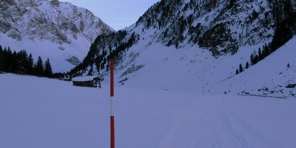 Der Weiterweg ist mit Schneestangen ausgesteckt und führt zur sichtbaren Talverengung.