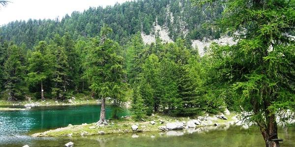 Der See schimmert in verschiedenen Grün- und Türkistönen